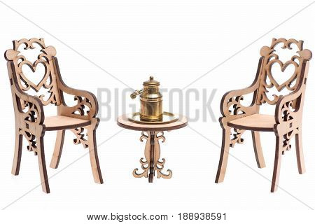 Antique concept. Milk can on golden tray on decorative engraved wooden table with chairs isolated on white background