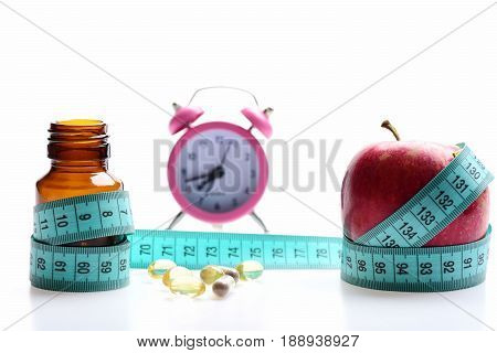 Apple And Glass Bottle Near Cod Liver Capsules And Clock