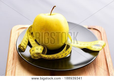 Apple, Big Ripe And Yellow, Standing On Black Ceramic Plate