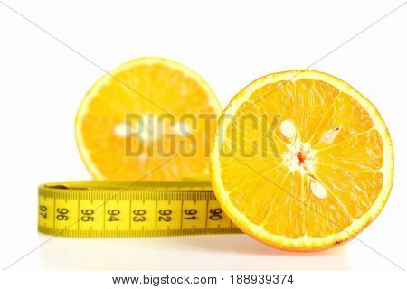 Halves Of Orange Fruit Together With Folded Yellow Measure Tape