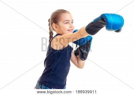 little girl stretches forward hand in large adult boxing gloves is isolated on a white background