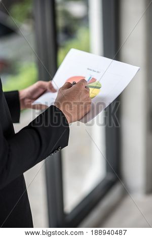 Close-up of Businessman checking financial graphs .
