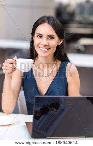Portrait of cheerful business woman drinking cup of coffee while sitting at table in confectionary shop. She having job with laptop