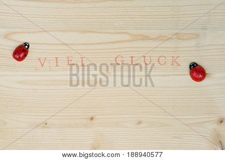 Stamped german text for Good luck on wood and ladybug, background