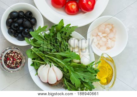 Ingredients for healthy salad. Tomatoes rucola (eruca sativa) spring onion mozzarella olives garlic and pepper with olive oil on a white stone background. Vegetarian food health or cooking concept. poster