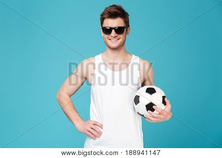Picture of young cheerful man standing over blue isolated background holding foot ball. Looking at camera.