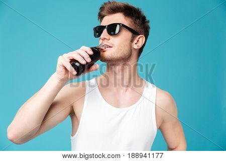 Photo of young handsome man standing over blue isolated background drinking aerated sweet water. Looking aside.