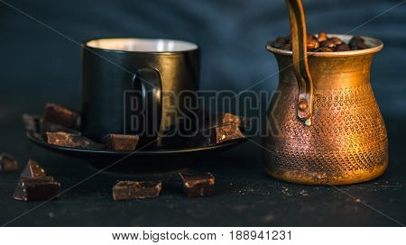 Coffee beans in copper coffee pot. Black coffee cup and chocolate broken into pieces on black slate surface