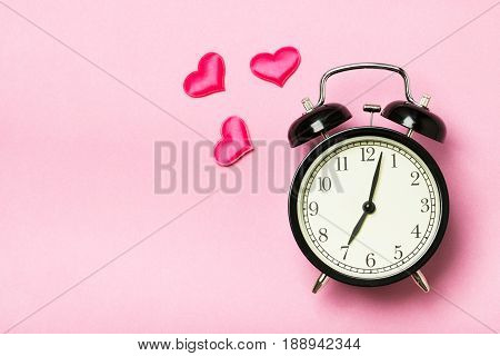 Alarm clock on a pink background symbolically ringing the hearts. The concept of the time of love the time of date the wedding the day of St. Valentine