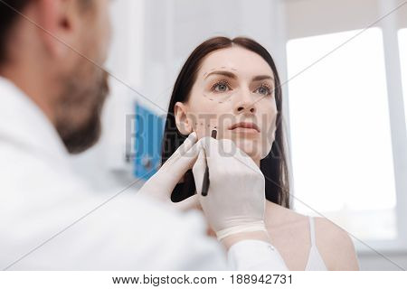 Architecting the look. Patient wonderful clever doctor getting ready for procedure and applying contours he needing correcting during lifting