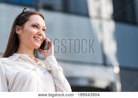 Low angle businesswoman demonstrating happiness while making conversation by phone