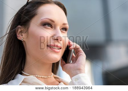 Portrait of lady expressing cheerfulness while telling by mobile