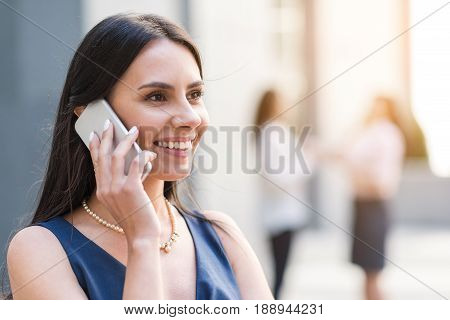 Female demonstrating happiness while making conversation by phone. She looking away