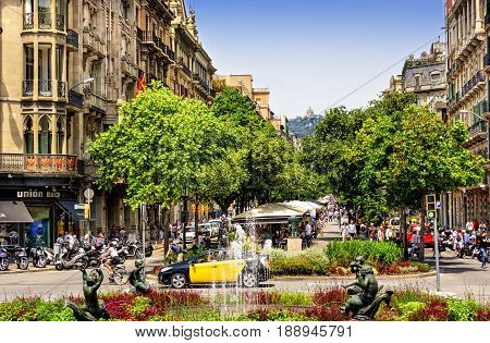 Barcelona Spain - June 6 2016: Busy La Rambla street filled with locals and tourists in the heart of the city of Barcelona.