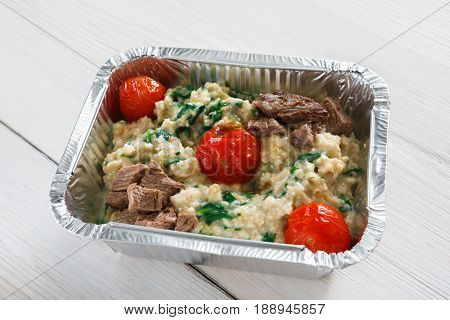 Healthy eating concept. Lunch foil box, take away organic food. Weight loss diet. Tomatoes and cereal on white wood, closeup