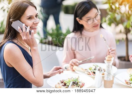 Side view business woman demonstrating happiness while speaking by mobile. She tasting salad in cafe