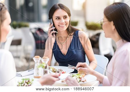 Cheerful female speaking by phone while eating dish at table. She locating near colleague in cafe