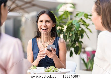 Outgoing woman expressing happiness while writing message in phone. She sitting at table in cafe