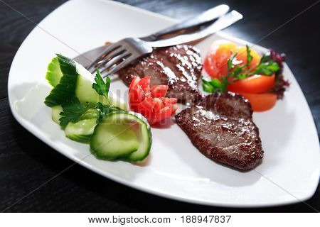 Plate with grilled meat and vegetables on dark wooden table