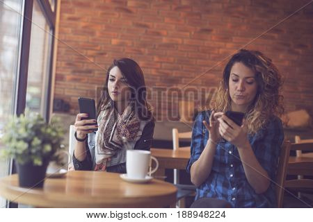 Two young women sitting in a cafe drinking their morning coffee and surfing the net on smart phones