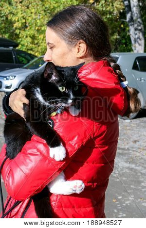 Young girl in red jacket is holding large black and white cat with harness in the autumn day.