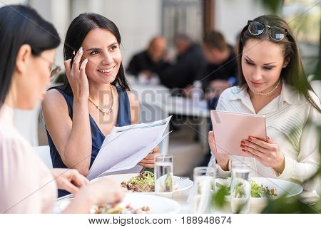 Cheerful woman thinking what to write. Smiling colleague watching at document. They sitting at table in confectionary shop