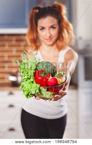 Beautiful caucasian girl holding glasses bowl with ingredients for low-caloric vegetables salad on kitchen. Selective focus. Vertical