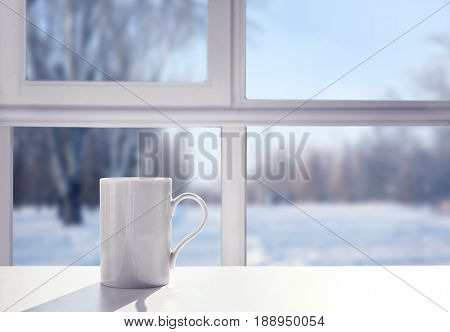 Cup of aromatic tea on windowsill. View of snowy forest from window
