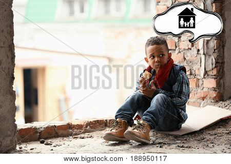 Little boy dreaming about family and home while eating bread in abandoned building. Poverty concept