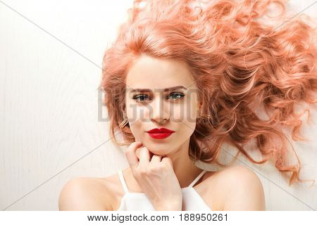 Trendy hairstyle ideas. Young woman with dyed apricot hair on white wooden background