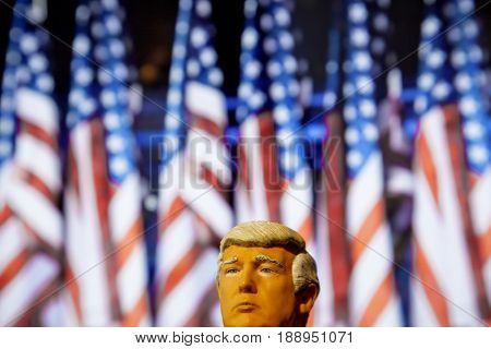 Caricature of United States President Donald Trump  - Head above water concept - using a toy action figure with US Flag backdrop