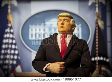 Caricature of United States President Donald Trump standing in front of White House press briefing podium - action figure toy