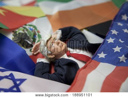 Caricature of United States President Donald Trump - Daydreaming of world power concept - on a bed of world country flags -  action figure toy