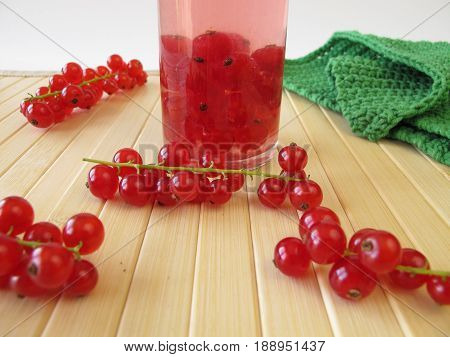 Red currant liqueur in bottle and fresh berries