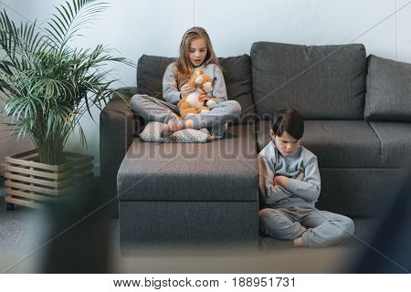Little Girl With Teddy Bear On Sofa And Boy Sitting With Arms Crossed