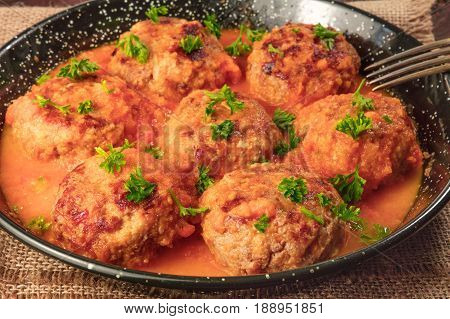 A closeup photo of meatballs in tomato sauce in a skillet