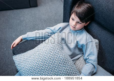 Tired little boy in pajamas holding pillows while sitting on sofa and looking away