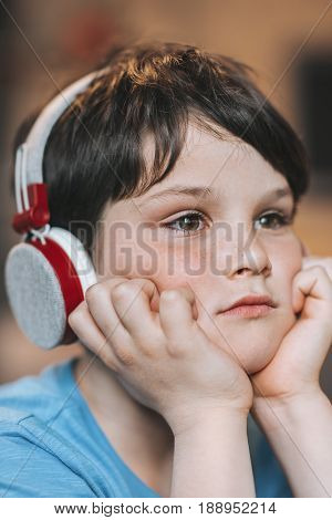 Pensive Kid Boy Listening Music In Headphones While Sitting At Home
