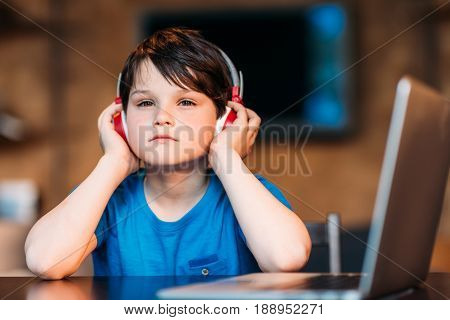 Portrait Of Thoughtful Little Boy Listening Music In Headphones