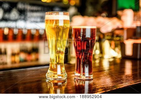 Glass Of Light And Dark Beer On A Pub With Bokeh Background
