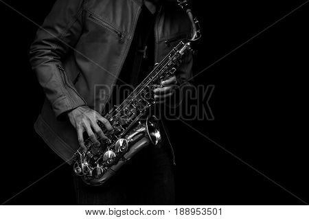 Male Jazz saxophone musician playing his instrument in the leather jacket. black and white color.