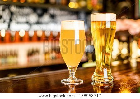 A two Glass of light beer on a pub with bokeh background.