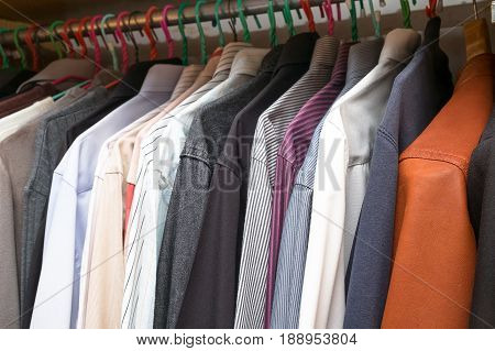 men simple clothing in the wardrobe of the many kind and colored clothes in house.