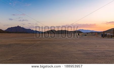 Wonderful landscapeArabian desert of stone Egypt with mountains at sunset.To the right of the desert nomad huts