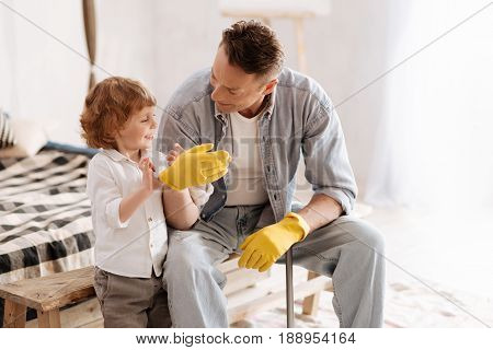 Preparing for clean. Attractive kid with curly hair keeping smile on his face and helping to put on rubber gloves to his daddy while looking forward