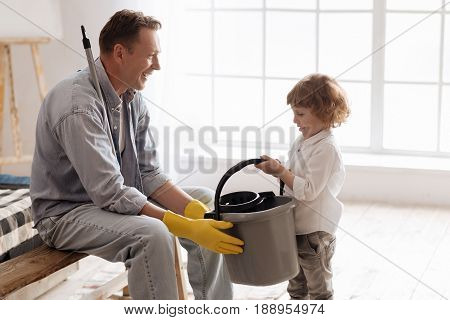Thank you. Positive delighted man wearing rubber gloves and sitting in semi position while taking grey bucket