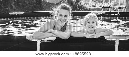 Happy Active Mother And Child In Swimming Pool Relaxing