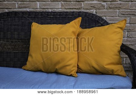 Wicker loveseat with summery yellow pillows and blue upholstery against an outdoor brick wall.