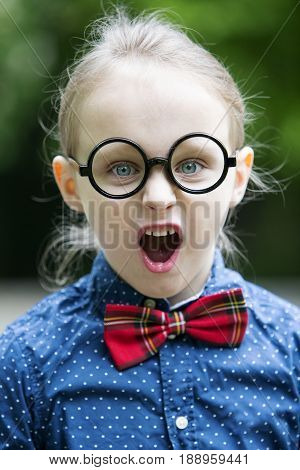 young blond boy with bowtie und big glasses is screaming