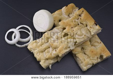white pizza with onions on the slate stone background